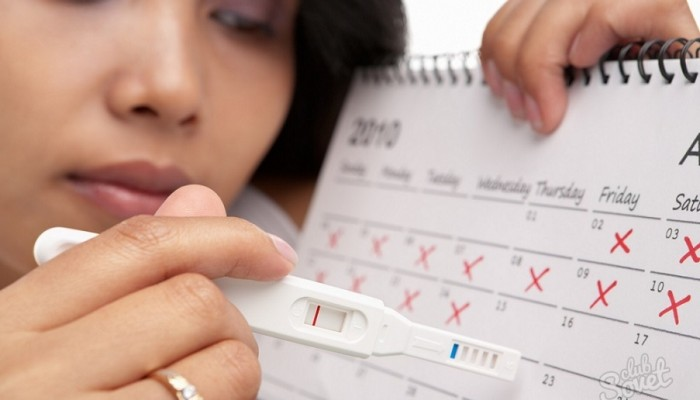Sad woman with negative pregnancy test and calendar. A concept being failed to get pregnant